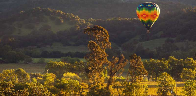 Hot air balloon sailing above the vineyard at Keever Vineyards in the Napa Valley